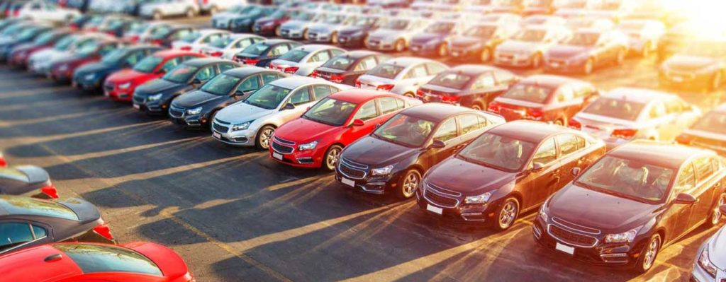 A fleet of cars parked at a dealership. Select DMV services renewals title transfer vehicle registrations boats motorcycles stickers plates